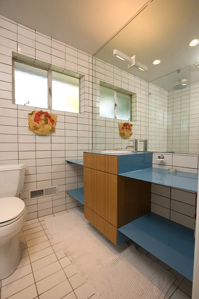 "Popp created wood cabinetry surrounded by another powder-coated steel vanity ""with a punch of blue"" for the bathroom. In anticipation of the project, he took time to gather key elements, such as the bathroom's Dornbracht faucet, at sale prices."