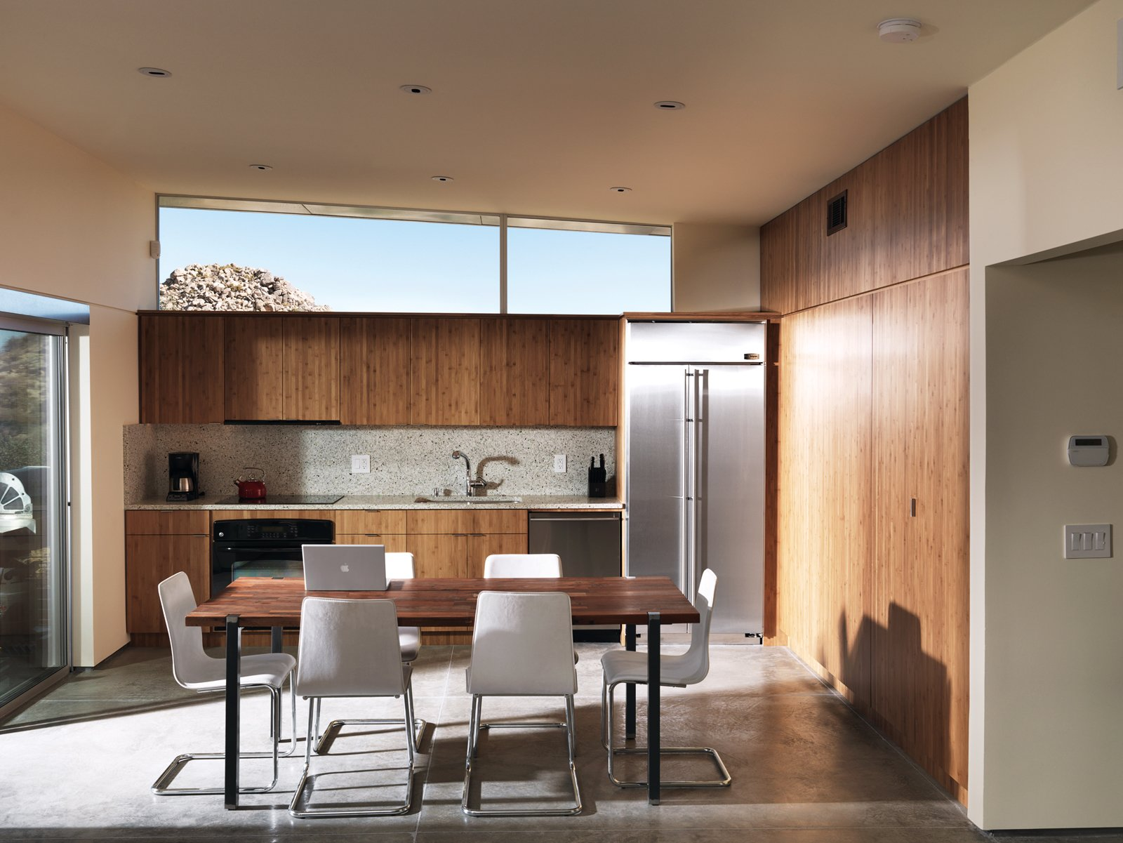 """One large room houses the kitchen, dining, and living area, the backsplash and countertops are made by Vetrazzo.  Photo 4 of 10 in Small """"Hybrid Prefab"""" Home in the Desert"""