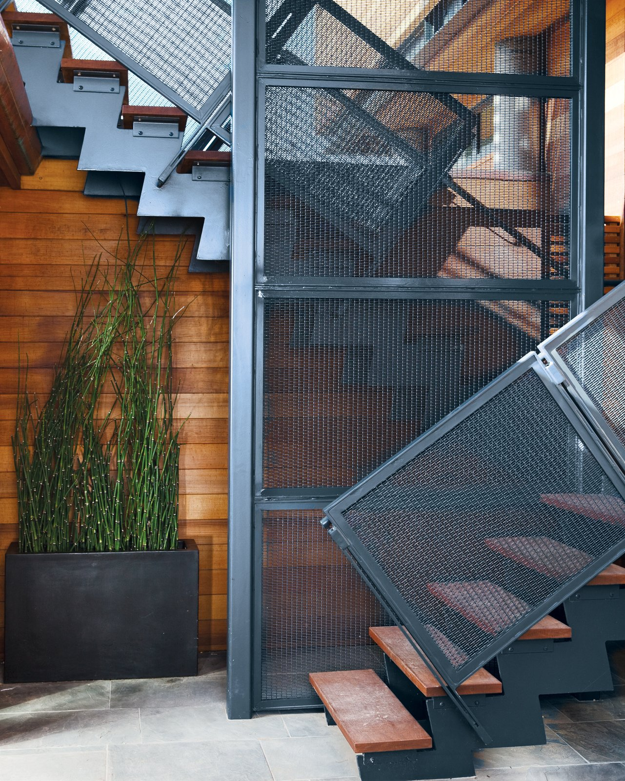 The steel stairwell that connects the garden-level patio with the new living space performs double duty as an anchor attached to the foundation.  Photo 8 of 10 in A Modern Coastal Home in Stinson Beach