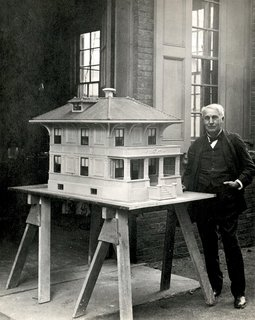 "Inventor Thomas Edison stands next to a model of a ""single-pour"" concrete home, a progenitor of today's prefab."