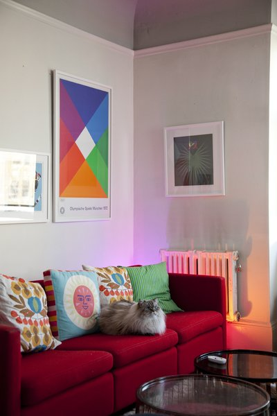 21 Cats Living in the Modern World - Photo 4 of 21 - In the living room, the LivingColors lamp, though obscured from view by a Knoll sofa by Charles Pfister, mimics the bright warm tones of the Max Bill poster. Grawe's cat, Eero, settles in amongst a collection of both vintage and contemporary pillows.
