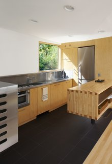 The stainless-steel-and-maple kitchen, which was completely pre-built as part of the module before being plopped onto the site, has a Flor-Gres recycled porcelain tile floor.