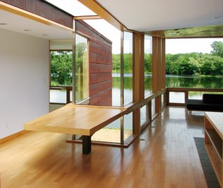 """The cross-section of the X, just off the kitchen, is outfitted with a cantilevered multi-use table and topped by a glass connector above. """"This makes the building seem larger, allows the outside to come in and makes for an interesting situation architecturally,"""" says Garrison."""
