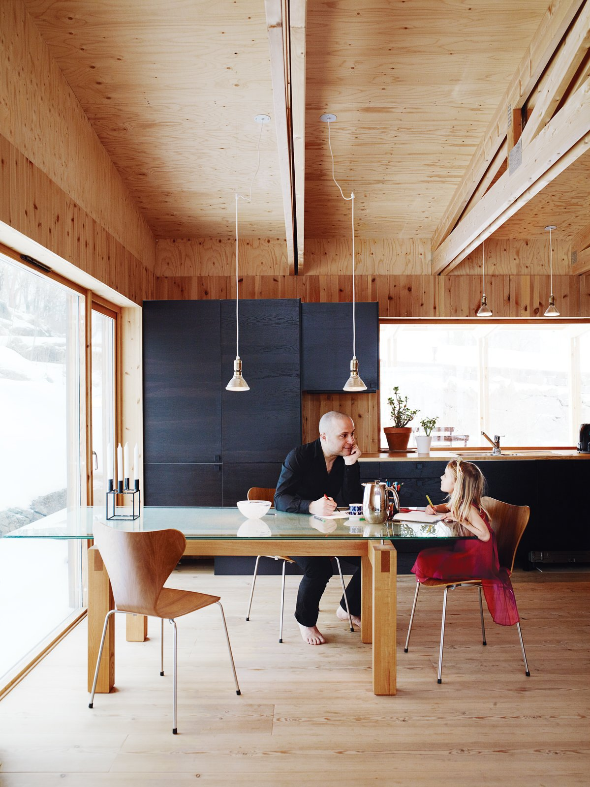 Dining Room, Pendant Lighting, Light Hardwood Floor, Table, and Chair Bornstein and his daughter Velma sit at a table the architect designed himself; the dining chairs were designed by Arne Jacobsen for Fritz Hansen.  Photo 1 of 1 in Minimalist Pine-Clad Dining Room in Sweden from Knotty by Nature