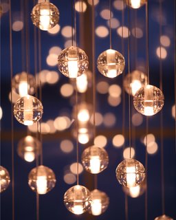 The 14 Series pendants are a family of low voltage lighting products designed for the Vancouver-based manufacturer Bocci. The pendants are articulated, seamed cast glass spheres with frosted cylindrical voids, into which a halogen light fixture is inserted. Unlike most contemporary lighting, the pendants are designed to be clustered in groups – suggesting tiny candles encased in floating spheres of water. The light interacts with the bubbles and imperfections of the cast glass to produce a rich halo of light. Photograph by Michael Boland.