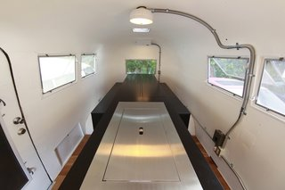 To maximize the small space inside the Airstream, Suzuki removed the existing structures and added a central island the follows his kenchikukagu style of design. Near the door (front of photo), a sink and cook top is hidden under the steel cover. At the rear (back of the photo), a dining table transforms into a set of twin beds. Photo by Sadamu Saito.