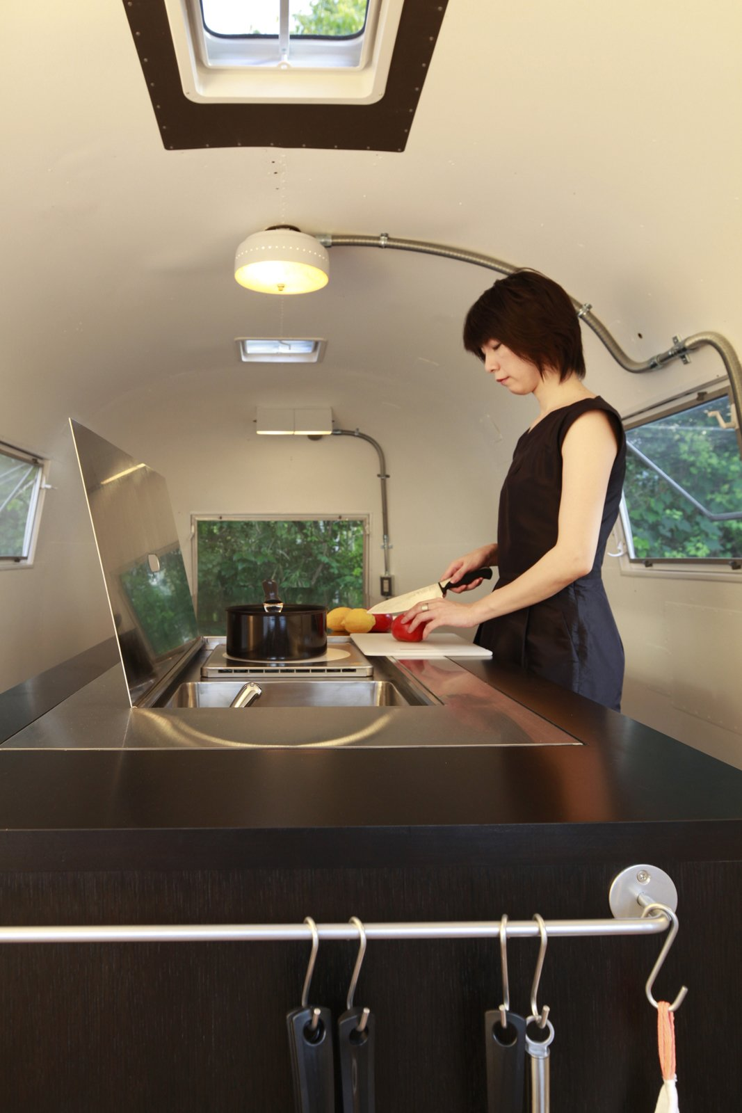 Kitchen, Cooktops, Drop In Sink, Metal Counter, and Ceiling Lighting Inside the renovated Airstream, a woman prepares a meal. The skylight above the cook top lets fumes escape the small space. Photo by Sadamu Saito.  Photo 8 of 8 in These 7 Vintage Airstreams Were Transformed Into Modern Escapes from Hide and Sleep