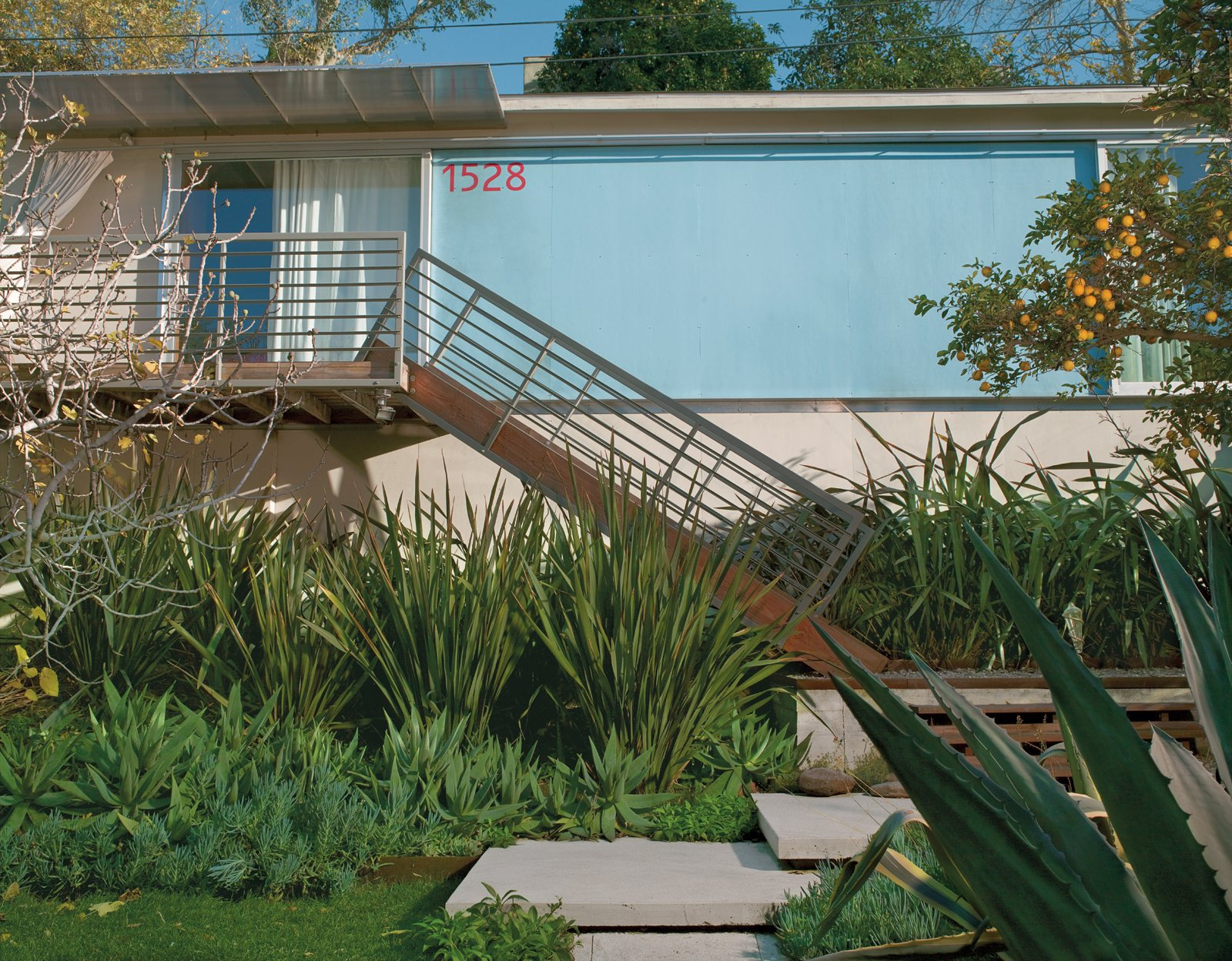 """Good Idea Studio redesigned the front facade with a welded tube steel staircase, an aluminum-and-polycarbonate awning, and fiber cement-board paneling painted """"Pool Party"""" blue.  Photo 4 of 11 in How Good Idea Studio Revamped a 1924 Clapboard House on a $62,000 Budget"""