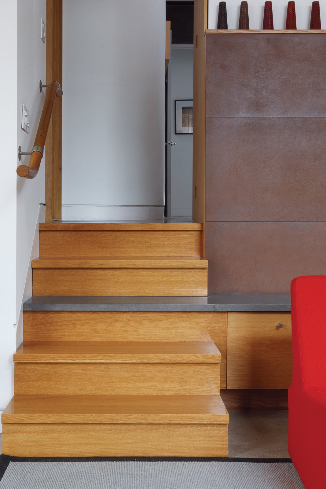 A staircase leads up to the main bedroom; the stairs and the fireplace were designed by Fleming with the architects.  Photo 2 of 8 in From Brown to Green