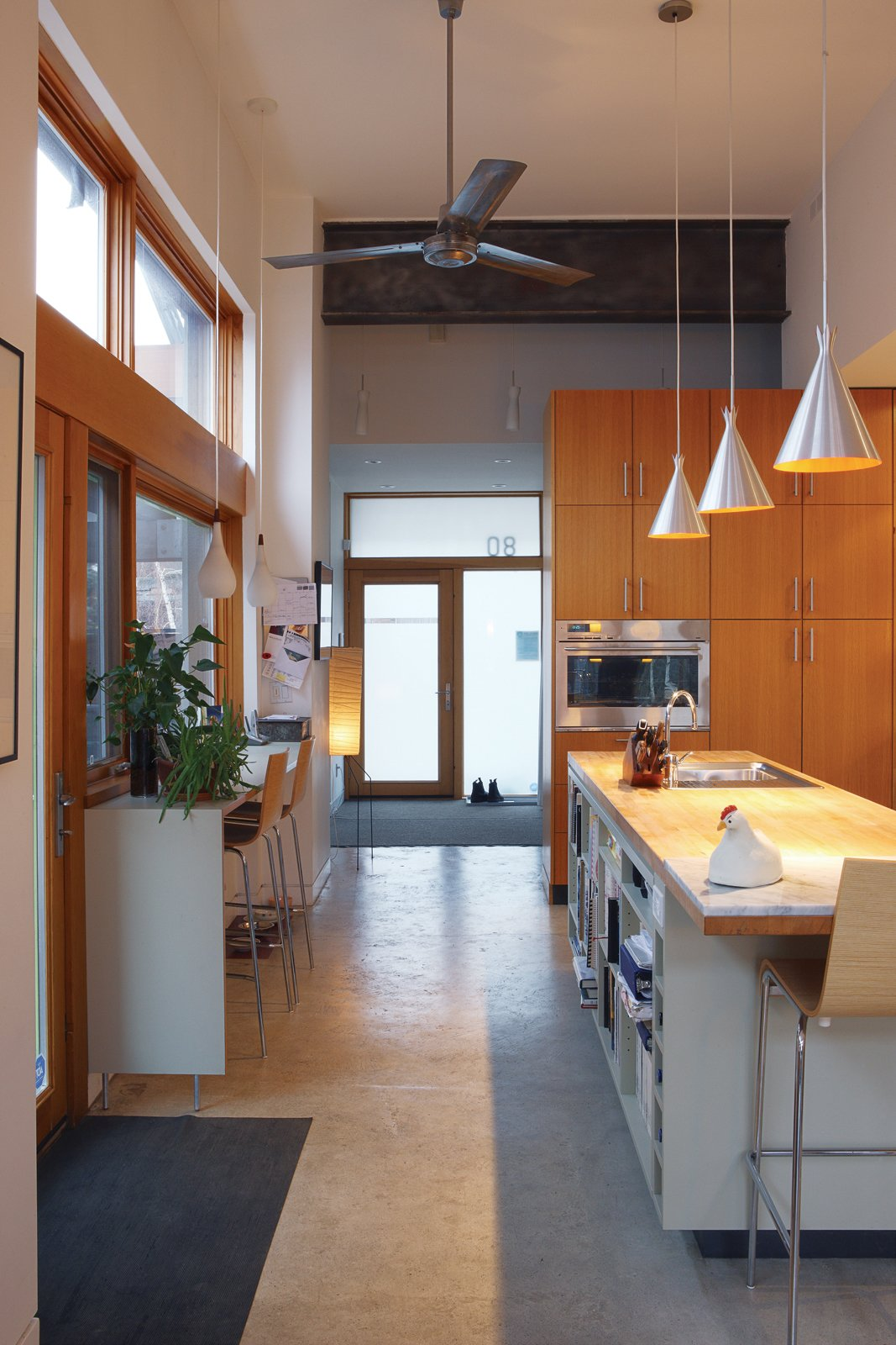 The kitchen, which gets light from three sides, welcomes guests into the house.  Photo 3 of 8 in From Brown to Green
