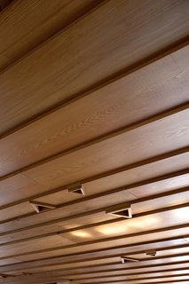 The cedar weatherboard ceiling in the living pavilion features triangular recesses for lightbulbs.