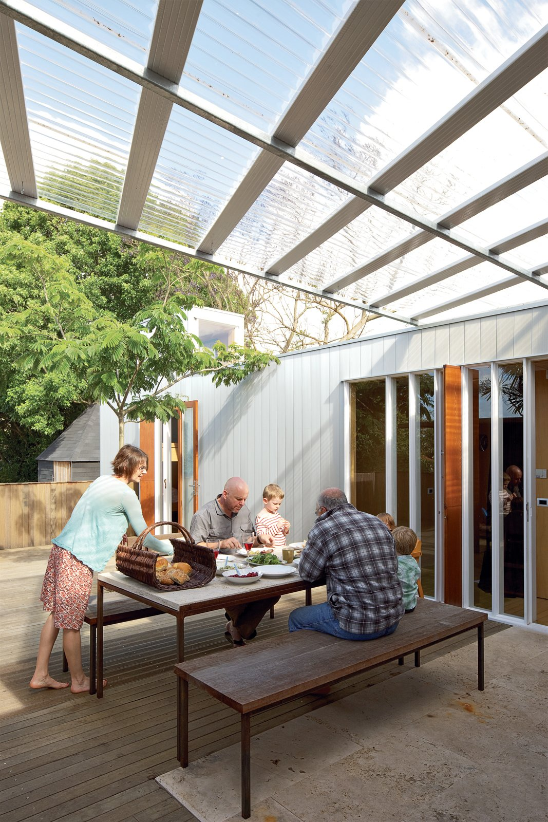 Outdoor and Wood Patio, Porch, Deck The family shares an alfresco lunch with Ikimau Ikimau, a friendly neighbor who helped build the house. The aluminum weatherboard cladding was custom-designed by O'Sullivan.  Photo 11 of 11 in The Great Compression