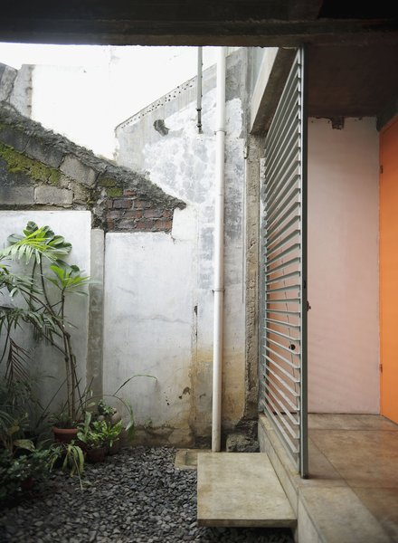 An orange door and metal grille make for a warm, if industrial, contrast to the stones and plants on the patio. They also weather well, something critical in a place where the climate leads to a palpable sense of decay.