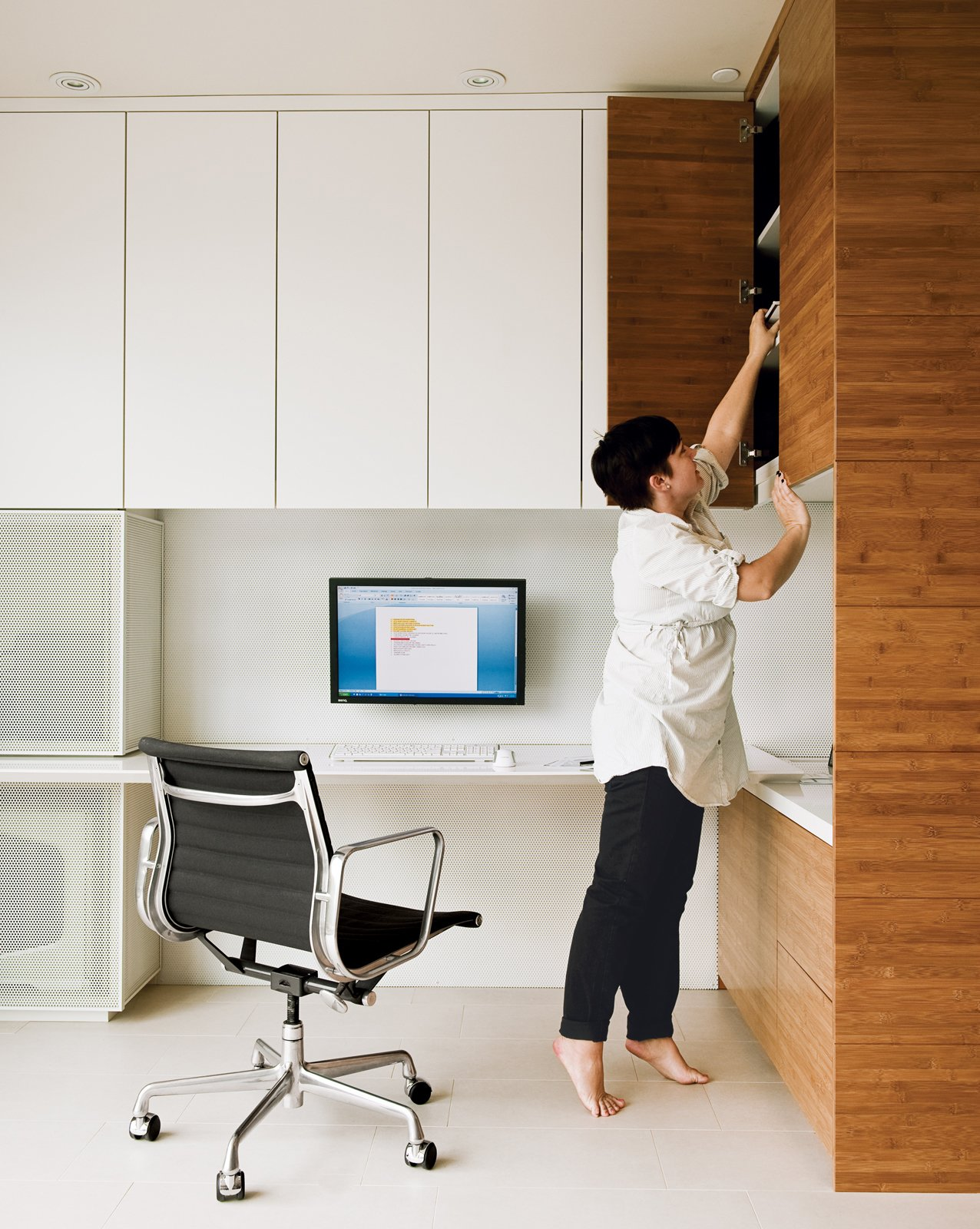 An Eames Aluminum Group chair for Herman Miller and bamboo shelving system are featured in the office Camille Owens and architect husband Francisco created within their living-dining space.  Photo 1 of 15 in Lucky 7