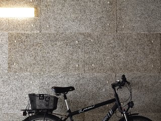 The lobby-cum-garage plays home to the couple's favorite forms of transport: <br><br>a bike and Spiekermann's Audi.