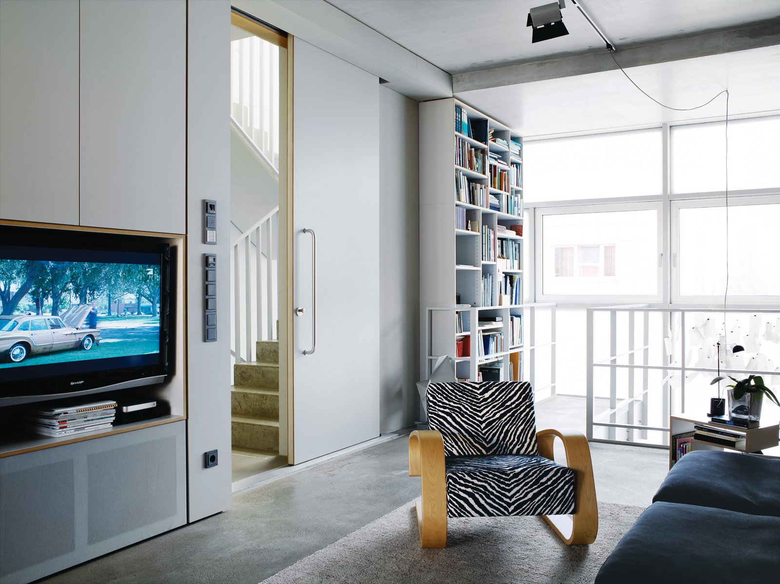 Living Room, Chair, Concrete Floor, and Bookcase Very large doors, like the one leading from the living area to the stairwell, add to the sense of space.  Photo 13 of 16 in A Rational Approach