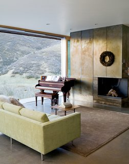 "In the living room, the canyon vistas share center stage with the wood-burning fireplace (attractive despite going through an ""awkward phase"") and a rare quarter-grand piano from the late 1800s, a Mooney family heirloom. The polished concrete floors are radiant-heated, powered by a small, highly efficient boiler in the basement."