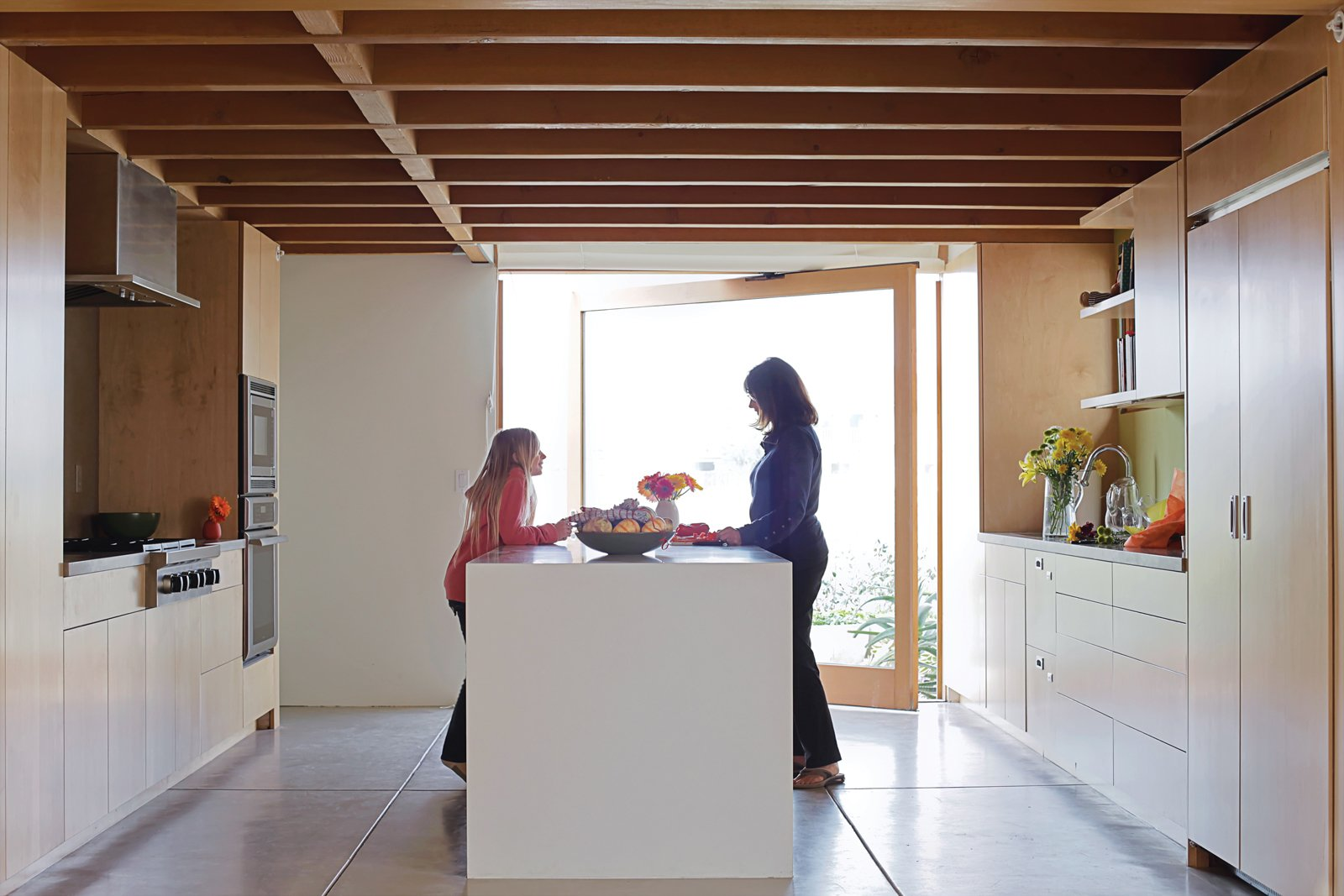 Kitchen Carole and granddaughter Allison—–silhouetted against a glass door that pivots open to the front garden—–plot how they'll prepare the family's next meal at the kitchen island.  Photo 7 of 13 in Coast Docs