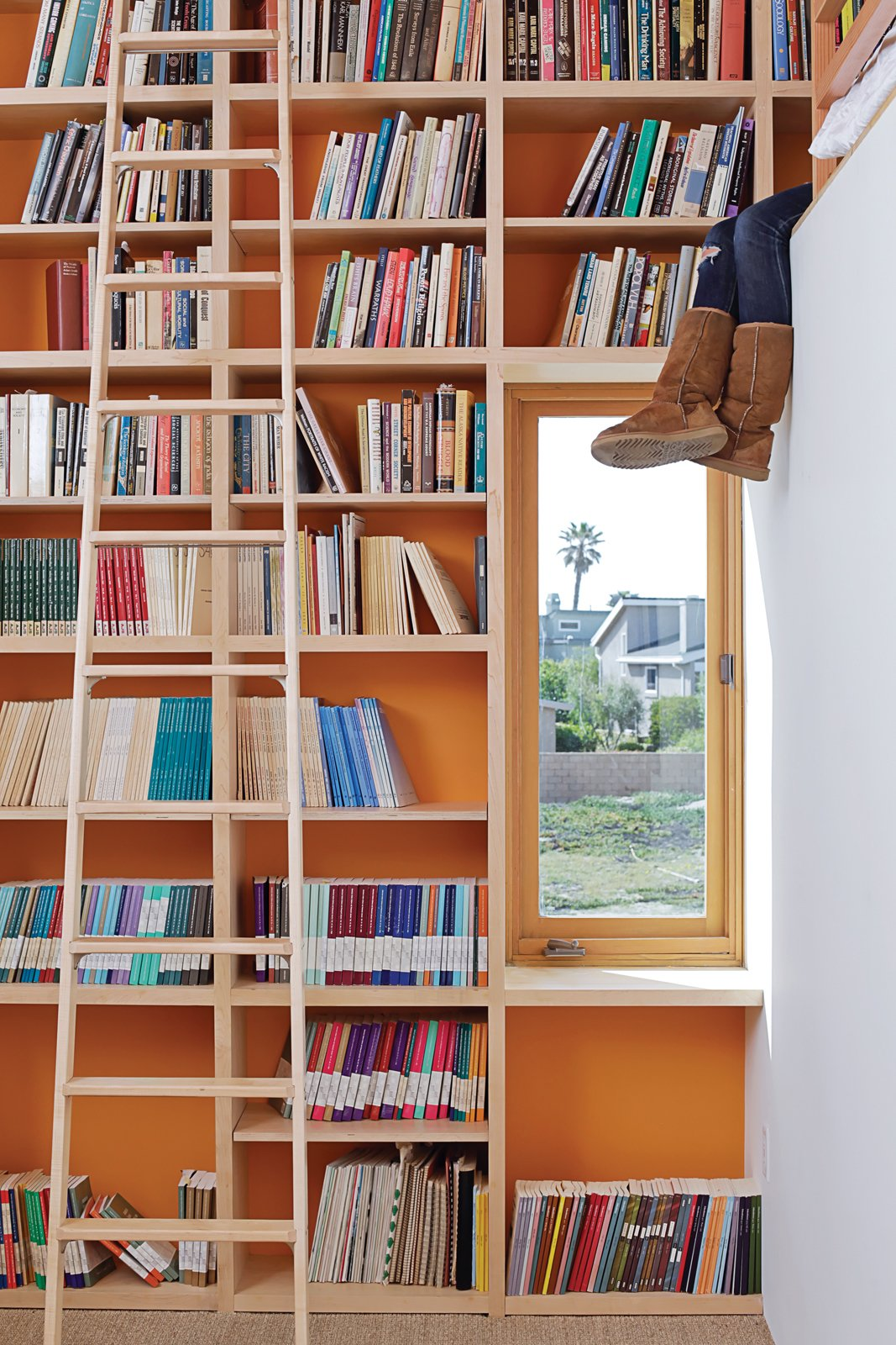 Storage Room and Shelves Storage Type To make the most of 13-foot-high ceilings that help draw hot air out through second-floor windows and doors, designer Daniel Garness painted select walls with playful color and lined them with maple plywood bookcases. Library ladders (about $1,500 each from Alaco Ladder Company) provide access to reading material and a sleeping loft.  Photo 2 of 13 in Coast Docs