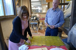 Catherine Bailey and Christopher Deam examine a tile board at Heath's factory.