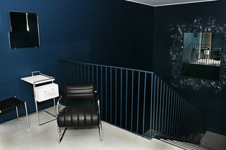 The dark, moody blue of this area's walls of a furniture showroom and gallery space in Toronto by George Yabu and Glenn Pushelberg are lightened by several mirrors on the walls, and broken up by a metal railing that's painted to match. On the top of the landing sits Eileen Gray's 1935 Bonaparte armchair and Petite Coiffeuse occasional table from 1929, whose chrome legs reflect light and the blue walls surrounding them.