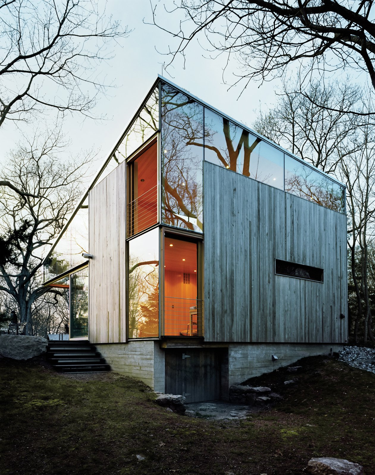 """Sheets of unframed glass fill the spaces between the building's operable windows and the sloping eave of the roof, giving the house, as architect Alan Organschi puts it, """"the feel of coming apart at the seams—of surfaces unhinged.""""  Photo 6 of 10 in Striking Angular Cottage in Connecticut"""