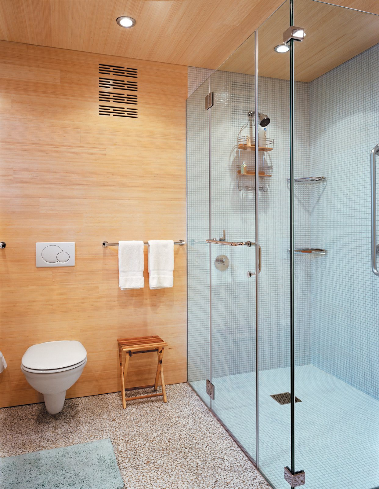 Bath Room, Terrazzo Floor, One Piece Toilet, Recessed Lighting, Enclosed Shower, and Ceramic Tile Wall The floors, walls, and ceilings are coated in FSC-Certified laminated bleached bamboo.  Photo 7 of 10 in Striking Angular Cottage in Connecticut