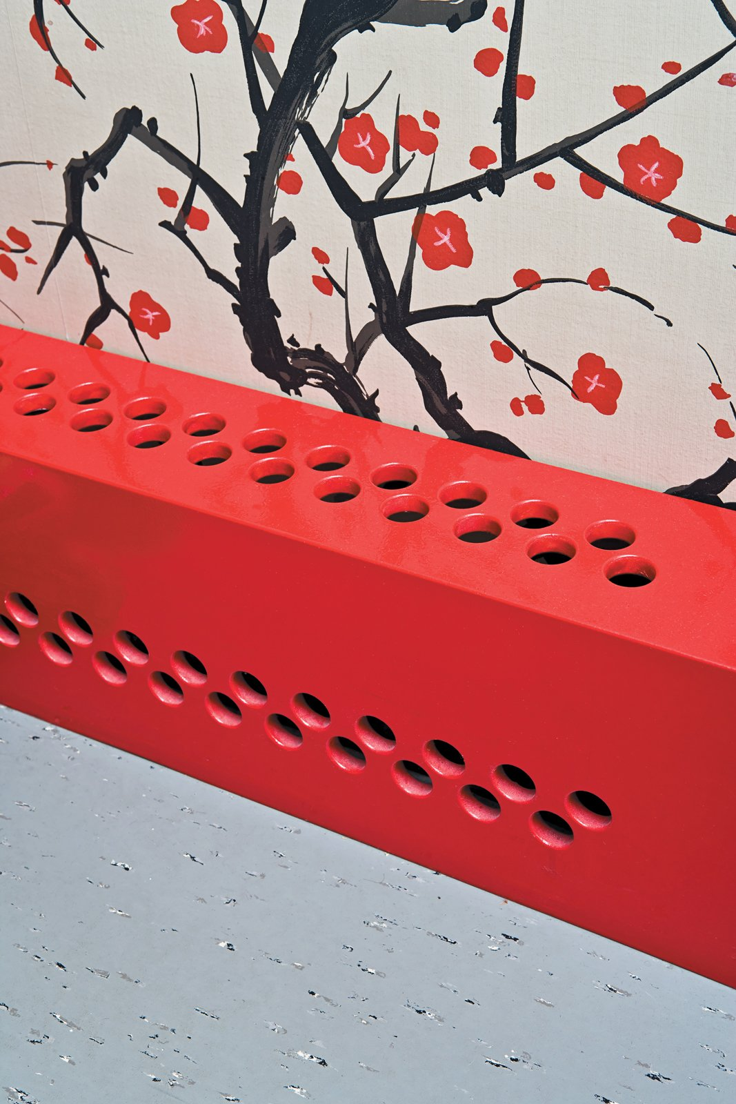The partial renovation gave Dine a few opportunities to experiment with future designs, like his custom radiator covers. Installed throughout the apartment to mask the old pipes, they're made from simple medium-density fiberboard panels (white in the living room and red under the wallpaper) that were CNC-milled with a dot pattern. Like the two storage towers in the living room, the covers consist of basic construction materials that Dine punched up with a coat of paint and a graphic detail.  Photo 9 of 12 in Fine Dine-ing