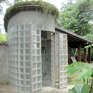 An outdoor shower in Costa Rica constructed by green homebuilder B-green Homes utilizes a mechanism for French doors from nearly two centuries ago that's sturdy enough to withstand the weight of glass block. The result is a unique shower with a grand entryway that lets natural light filter through.