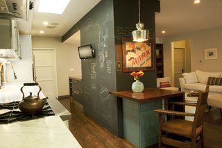 Architectural designers Chinmaya Misra and Apurva Pande retained the existing structural fireplace wall inside, now sheathed in useful chalkboard paneling, then knocked down a light-blocking wall between the living area and the kitchen and introduced new millwork and appliances to the space. The door at left leads to the garage; at right is the door to the couple's former bedroom.