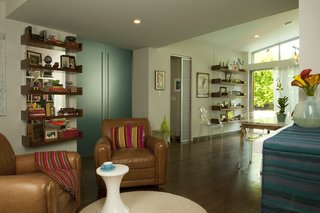 A view from the living area toward the addition, and the transition of old to new. The existing study, where Lyall often writes, is reached through the new opaque teal doors that slide into the wall (one slides behind the open bookshelf at left). Beyond the sliding white door is the master bedroom and bathroom.