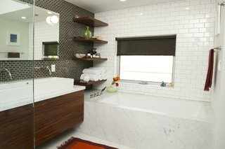 """Misra notes that in the master bath, """"Elizabeth and Edgar wanted a muted palette."""" This was achieved with white subway tile and a smaller brown tile from Interceramic that echoed the larger-scale tile. """"We saw the little Jasper Morrison ball lights in London and then couldn't find them again,"""" says Lyall. """"We finally came across them at a store on Melrose in LA, and bought them after obsessing over them for awhile."""" The fixtures are by Rohl; the sink is from Duravit."""