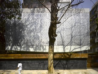 "Working within the restraints of the sometimes-severe Mumbai weather and around the city's great architectural varieties, not to mention the existing coconut palms and banyan trees, architectural firm Khanna Schultz constructed a 27,000-square-foot-plus, seven-unit modern apartment building with a striking open-air base. At front is the street-side boundary wall made up of a stone base and a planter on top, which is meant to fill in with foliage over time. The curved base of the building is cantilevered about 10 feet. ""This has to do with zoning and fire codes,"" notes Schultz. ""But since you don't see the columns, it seems like the whole building is floating."""