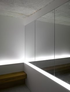 """A Modern Aesthetic in Mumbai - Photo 10 of 17 - A mirror near the mailboxes in the lobby gives the illusion of more space. A team from Lighting Planners Associates, based in Japan, added the uplights behind the bench for effect. The architectural firm left the ceilings raw concrete to make the space """"more enigmatic,"""" says Schultz."""