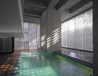 A Modern Aesthetic in Mumbai - Photo 12 of 17 - The aluminum casing creates a play of light and shadows as the sun moves across the building. A lap pool, at right, spills over into the main pool.