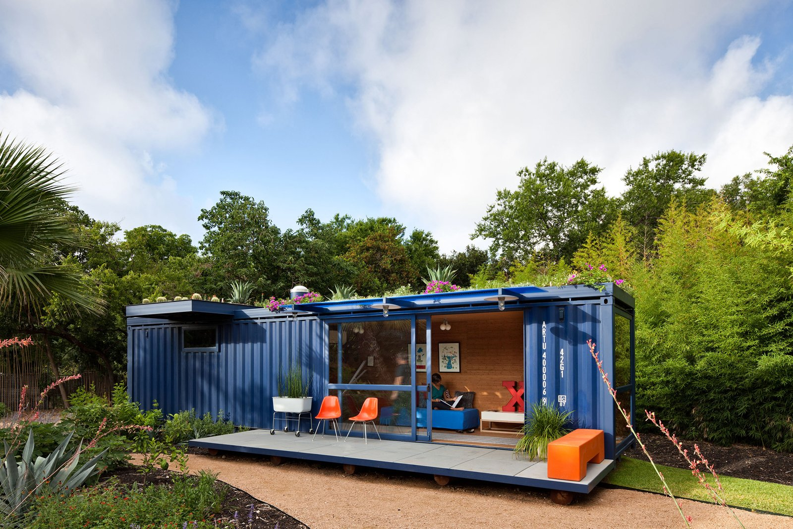 """Outdoor, Small Patio, Porch, Deck, Walkways, Grass, and Gardens """"In the beginning I really wanted the container to be off the grid but solar is still very expensive in San Antonio, especially for small spaces,"""" says Hill. """"The green roof was an element that I had not thought of at the beginning, but as it turns out saves me more money on air-conditioning than the solar would have, and is a lot prettier.""""  Photo 2 of 10 in 9 Small Spaces With  Color from Smaller in Texas"""
