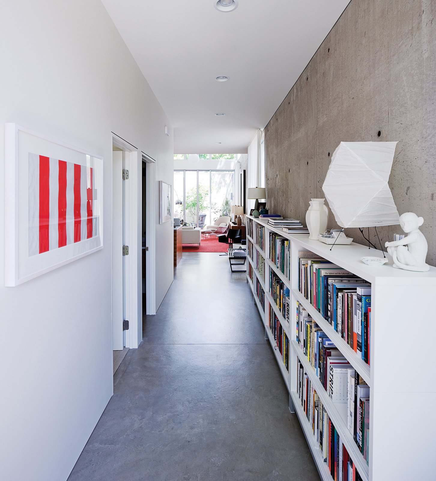 Hallway and Concrete Floor A portion of Blauvelt's 3,000-book library is archived in the long entry hall where the geometry of a Noguchi lamp plays off a pair of minimalist prints by Daniel Buren.  Photo 1 of 29 in Modern Urban Retreat in South Minneapolis