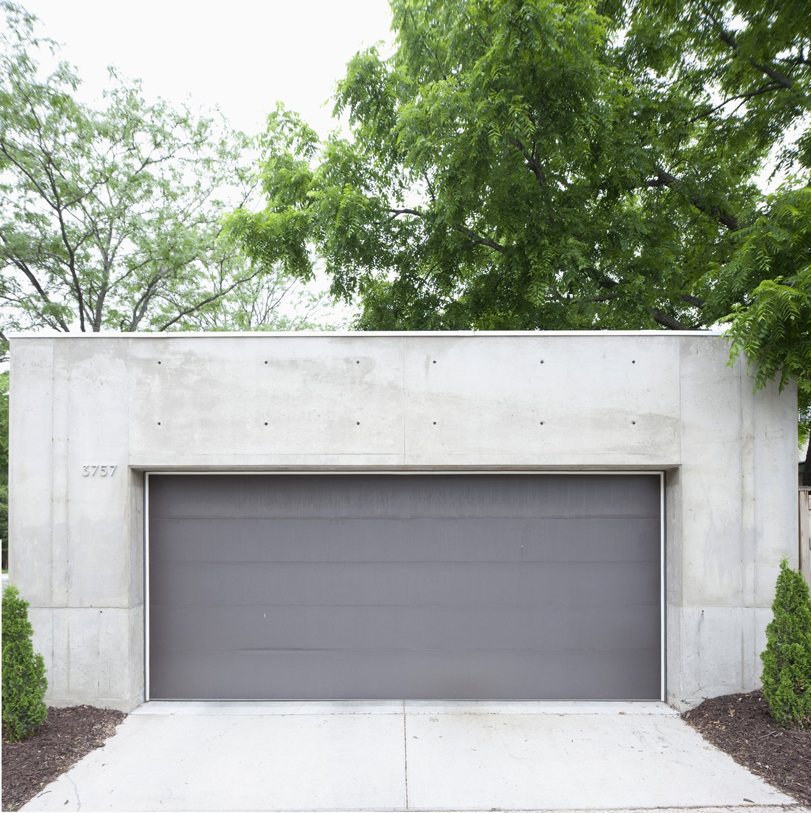 Garage and Detached Garage Room Type The darker gray garage door offers a chromatic and textural contrast to the concrete shell.  Photo 24 of 29 in Modern Urban Retreat in South Minneapolis