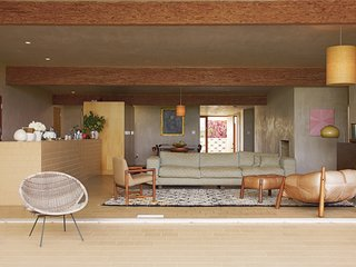 Pearson and Trent furnished the house with lamps and chairs they culled from vintage stores in the area. They found the overstuffed leather lounger at Surfing Cowboys in Venice. The couple and the architects collaborated on the couch design and had it fabricated. Works by local artists fill their home, such as the white vessels by California-based, Japanese-born ceramicist Shio Kusaka.