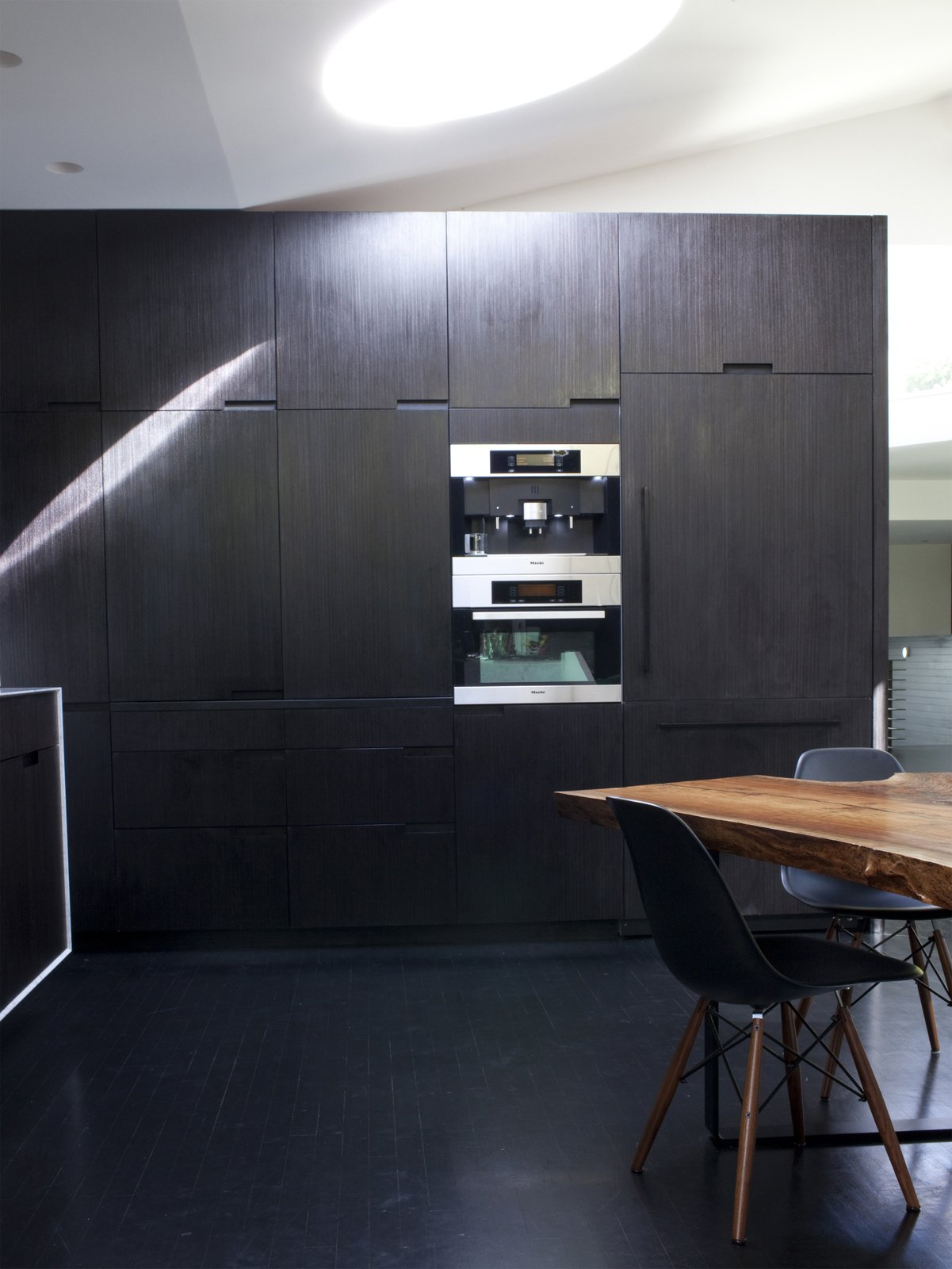 Kitchen, Wall Oven, and Dark Hardwood Floor A wall of built-ins in the kitchen houses a raft of Miele appliances including a refrigerator, microwave, and espresso machine.  Photo 10 of 11 in 10 Stunning Ways to Use Black in Your Kitchen from Designed In-House