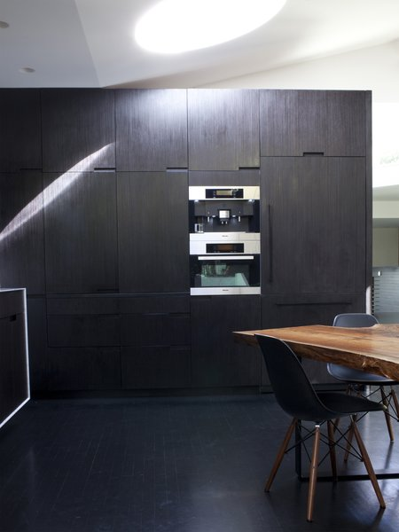 A wall of built-ins in the kitchen houses a raft of Miele appliances including a refrigerator, microwave, and espresso machine.