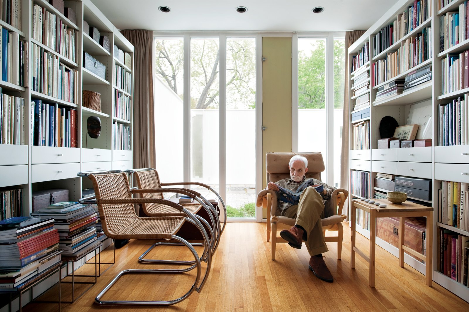 The library is lit by the front courtyard. The chartreuse vent, originally painted vermilion, is the one architectural color inside the house. Two Cantilever Cane chairs by Mies van der Rohe face Isaacson as he rests upon a Pernilla easy chair by Bruno Mathsson.  Photo 1 of 8 in The House of a Lifetime