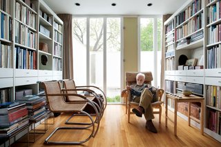 The library is lit by the front courtyard. The chartreuse vent, originally painted vermilion, is the one architectural color inside the house. Two Cantilever Cane chairs by Mies van der Rohe face Isaacson as he rests upon a Pernilla easy chair by Bruno Mathsson.
