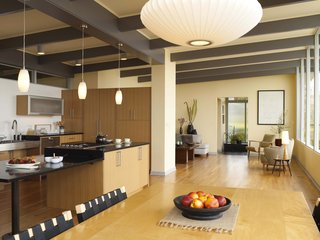 A view from the dining area. The architects arranged for the large original fireplace to be taken down to maximize space, and added a new dividing wall between the living room and the kitchen. The island, outfitted with a gas cooktop from Fisher, is new. Its surface extends to an adjacent workspace, beneath which is plenty of clearance for wheelchairs or stools.