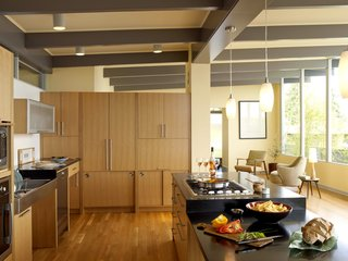 "The kitchen cabinet wall provides storage and workspace, yet retains an open feel by stopping well beneath the ceiling. Sliding cabinets at the bottom reduce the number of space-hogging swinging cabinet doors, and a KitchenAid mixer is hidden behind the horizontal lift-up cabinet at right, which recesses into the wall. ""The cooktop is at a height where I can see into my pot of spaghetti sauce,"" says Braitmayer. ""I cook in this kitchen more than ever before."" The countertops are heat-resistant, allowing more options for the person cooking. To the right of the sink is an ADA-compliant dishwasher from Miele. The pendant lights are from Progress Lighting."