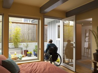 "The new, more intimately scaled master bedroom leads to an adjacent patio, which was repaved to gently slope from the doorway to new drains, which solved both an access and a water issue. Braitmayer planted quick-growing bamboo in galvanized troughs for privacy. At right is the seamless passage to the master bathroom. ""There are no longer raised thresholds in the house,"" notes Braitmayer."