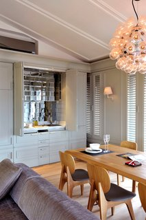 The living and dining room of a recent residential project, featuring a Castiglioni lamp and a mirrored bar.
