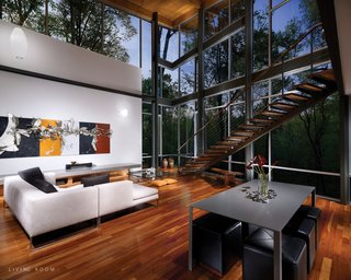 The entrance progresses from the top of the hill, across a bridge and into a balcony foyer. There the forest fills the interior through north-facing glass walls. A stair descends past the glass to the main living floor, which opens onto a partially secluded south-facing terrace below the bridge.