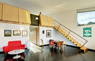 Wong's photographs dot the living area/studio; a painting by Li is at right. The architects put in a black concrete floor and designed the overhead birch-ply blocks, which double as bookcases for the upstairs sleeping loft. Accompanying a Saarinen Tulip table is a loveseat from Palazetti. Architect Michael Graves designed the chair with the circular cutout; opposite it is one designed by architect Jim Wallace for Novikoff, and the pair of red-and-white Catifa chairs are from Arper. The stair is made from Radiata plywood.