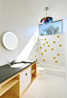 """Light floods the second-floor bath, which is housed within a birch-ply """"box"""" also containing storage. The water is heated by a tankless, on-demand unit from Rinnai. The architects continued the tile motif for the bath downstairs; the honey-colored tiles are from Dal-Tile. The lamp is by Kathleen Ash of Studio K Glass."""